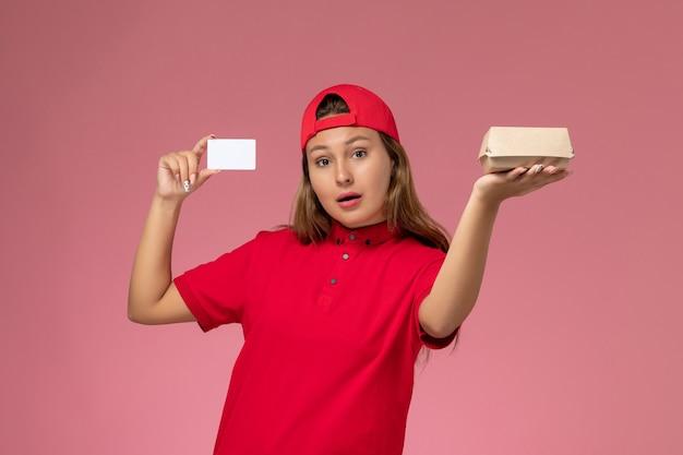 Vooraanzicht vrouwelijke koerier in rood uniform en cape die weinig voedselpakket en kaartje vasthoudt op lichtroze muur, uniforme bezorgdienst voor baanmedewerkers