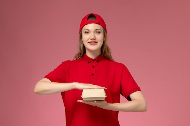 Vooraanzicht vrouwelijke koerier in rood uniform en cape die weinig voedselpakket voor bezorging op de lichtroze muur houdt, uniforme baan van bezorgbedrijf
