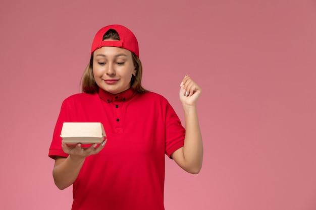 Vooraanzicht vrouwelijke koerier in rood uniform en cape die weinig voedselpakket voor bezorging op lichtroze bureau uniform bezorgbedrijf houdt