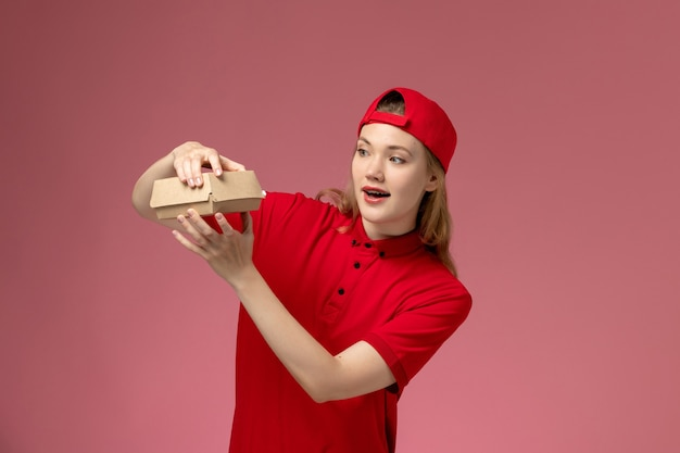 Vooraanzicht vrouwelijke koerier in rood uniform en cape die weinig voedselpakket voor bezorging op roze muur, uniforme baan van bezorgbedrijf houdt en opent