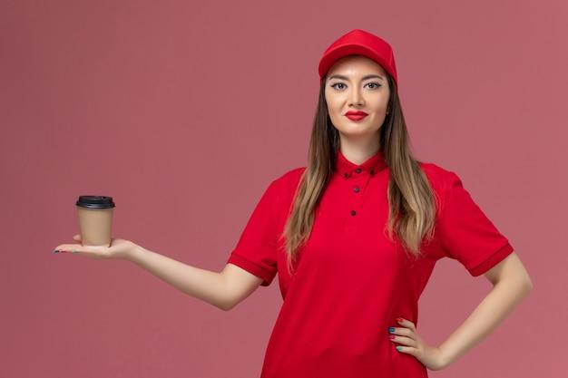 Vooraanzicht vrouwelijke koerier in rood uniform en cape levering koffiekopje op roze achtergrond service levering uniforme werknemer te houden