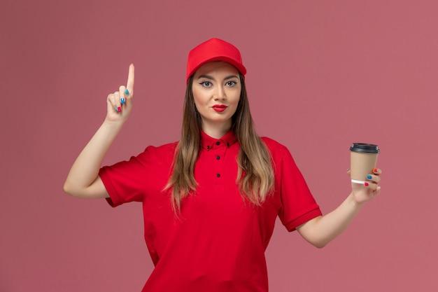 Vooraanzicht vrouwelijke koerier in rood uniform en cape met bezorging koffiekopje met opgeheven vinger op de roze achtergrond service levering uniform