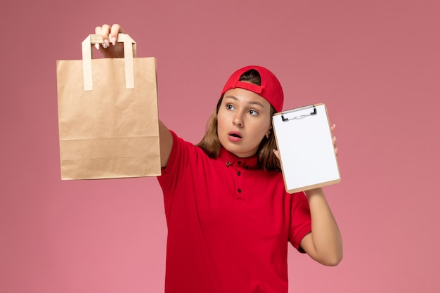 Vooraanzicht vrouwelijke koerier in rood uniform en cape met bezorgingsvoedselpakket met blocnote op lichtroze muur, uniforme bezorgdienst