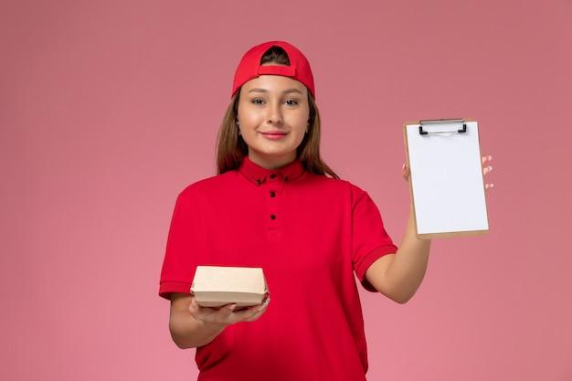Vooraanzicht vrouwelijke koerier in rood uniform en cape met klein pakket met voedsel voor bezorging en blocnote op de roze muur, uniform bezorgbedrijf