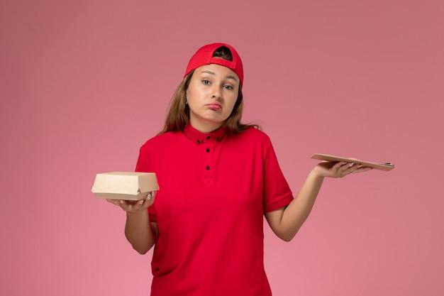 Vooraanzicht vrouwelijke koerier in rood uniform en cape met klein pakket met voedsel voor bezorging en blocnote op roze muur, bedrijf voor uniforme bezorgdienst