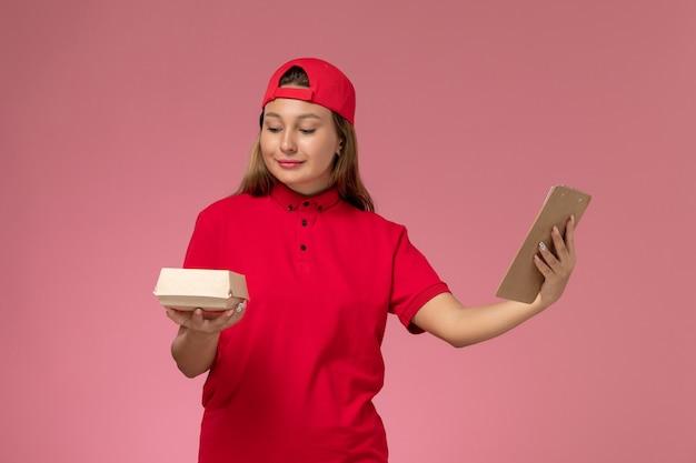 Vooraanzicht vrouwelijke koerier in rood uniform en cape met klein voedselpakket en blocnote op roze muur, uniform bezorger servicebedrijf