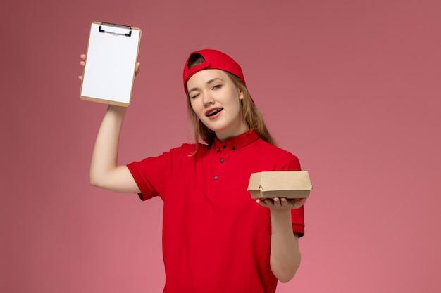 Vooraanzicht vrouwelijke koerier in rood uniform en cape met klein voedselpakket voor bezorging met blocnote knipogen op roze muur, baanuniform van bezorgbedrijf