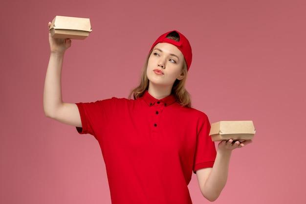 Vooraanzicht vrouwelijke koerier in rood uniform en cape met kleine bezorgvoedselpakketten op lichtroze muur, bezorgdienst werknemer bedrijf uniforme baan