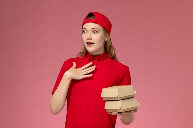 Vooraanzicht vrouwelijke koerier in rood uniform en cape met kleine bezorgvoedselpakketten op lichtroze muur, uniform werk van het bezorgbedrijf