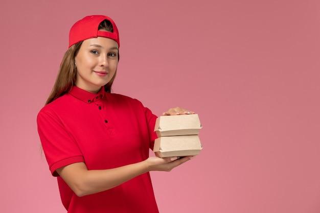 Vooraanzicht vrouwelijke koerier in rood uniform en cape met kleine bezorgvoedselpakketten op lichtroze muur, uniforme baanbezorgservice