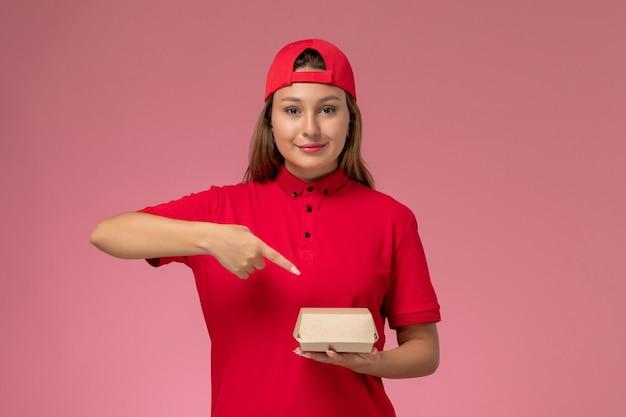 Vooraanzicht vrouwelijke koerier in rood uniform en cape met levering voedselpakket op lichtroze achtergrond uniforme baan van het bezorgbedrijf