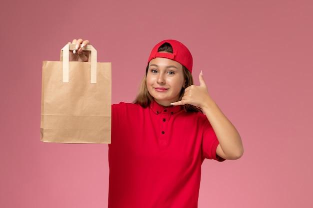 Vooraanzicht vrouwelijke koerier in rood uniform en cape met leveringspapierpakket op de roze muur, uniforme bezorgdienst