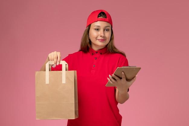 Vooraanzicht vrouwelijke koerier in rood uniform en cape met voedselpakket voor bezorging en blocnote op lichtroze muur, uniforme bezorgdienst