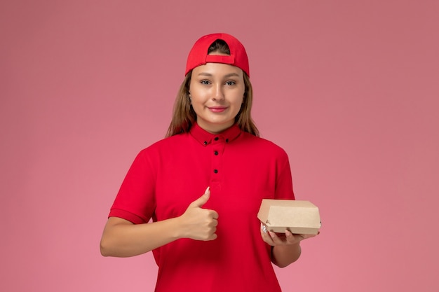 Vooraanzicht vrouwelijke koerier in rood uniform en cape met voedselpakket voor bezorging en glimlachend op de roze muur, uniforme baan van het bezorgbedrijf