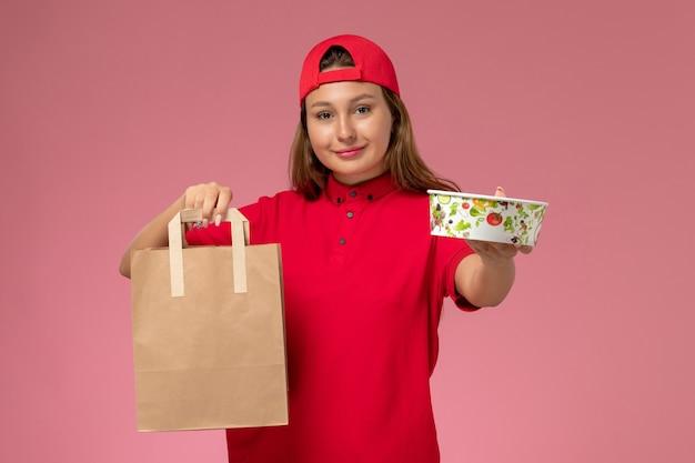 Vooraanzicht vrouwelijke koerier in rood uniform en cape met voedselpakket voor bezorging en kom op de roze muur, uniforme bezorgdienst