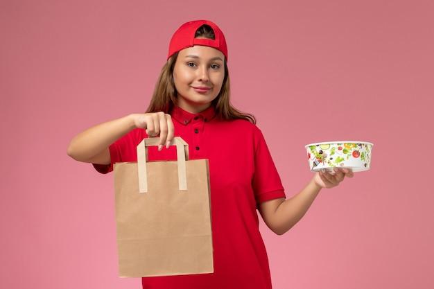 Vooraanzicht vrouwelijke koerier in rood uniform en cape met voedselpakket voor bezorging en kom op de roze muur, uniforme bezorgservice