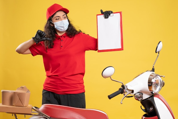 Vooraanzicht vrouwelijke koerier in rood uniform met bestandsnotitie op de gele achtergrond levering covid-service uniform werknemer pandemische baan