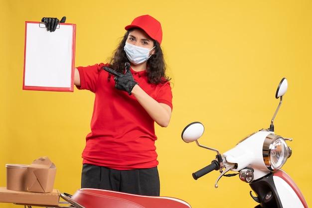Vooraanzicht vrouwelijke koerier in rood uniform met bestandsnotitie op gele achtergrond levering covid-service uniform pandemische baan