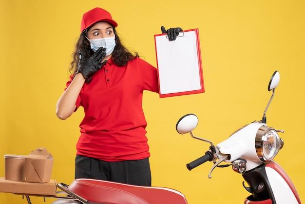 Vooraanzicht vrouwelijke koerier in rood uniform met bestandsnotitie op gele vloer levering covid- service uniform werknemer pandemische baan
