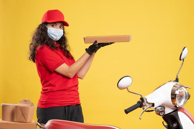 Vooraanzicht vrouwelijke koerier in rood uniform met pizzadoos op gele achtergrond werknemer levering covid-pandemische service virus baan