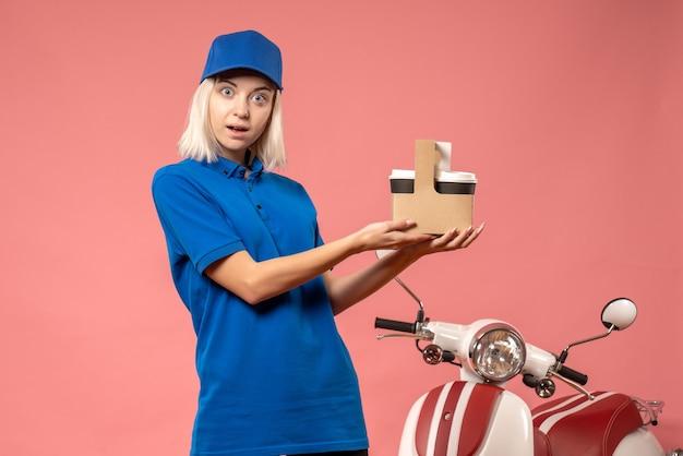 Vooraanzicht vrouwelijke koerier koffie op het roze te houden