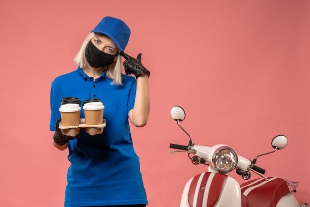 Vooraanzicht vrouwelijke koerier koffiekopjes op roze te houden