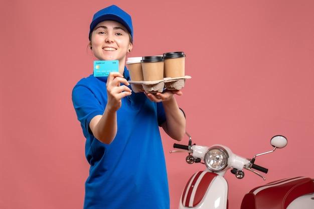 Vooraanzicht vrouwelijke koerier met bezorgkoffie en bankkaart op roze werk levering baan fiets uniforme servicemedewerker