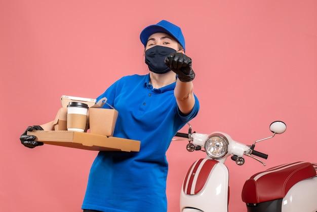 Vooraanzicht vrouwelijke koerier met bezorgkoffie en eten op een roze pandemie werk bezorger covid-uniforme baan service