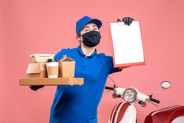 Vooraanzicht vrouwelijke koerier met bezorgkoffie en eten op roze pandemie werk bezorgdienst werknemer covid-uniform baan