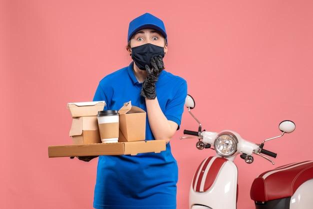 Vooraanzicht vrouwelijke koerier met bezorgkoffie en eten op roze pandemie werk bezorging covid-uniforme baandienst Gratis Foto