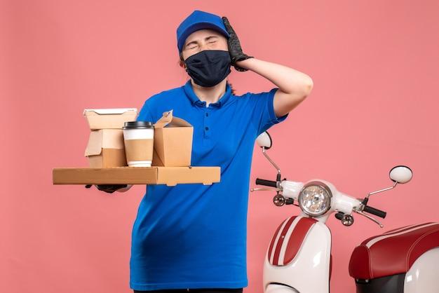 Vooraanzicht vrouwelijke koerier met bezorgkoffie en voedsel op roze pandemische werkarbeider covid-uniforme baandienst