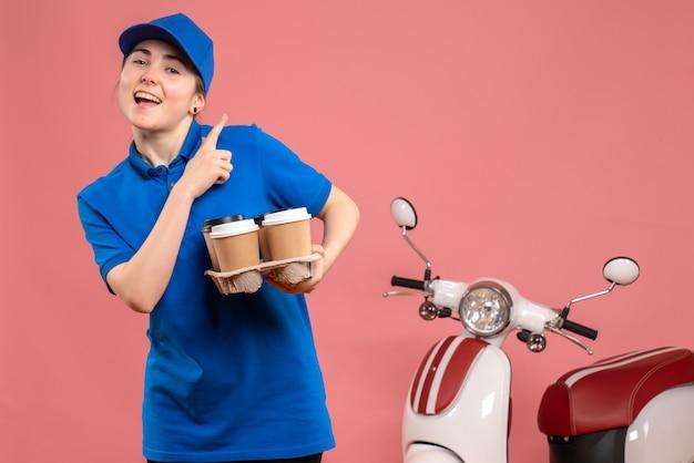 Vooraanzicht vrouwelijke koerier met bezorgkoffie op de roze fiets van de de arbeidsdienstarbeider van de werklevering
