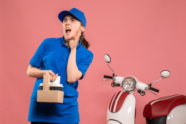 Vooraanzicht vrouwelijke koerier met bezorgkoffie op een roze werk bezorgdienst werknemer vrouw fiets uniform baan