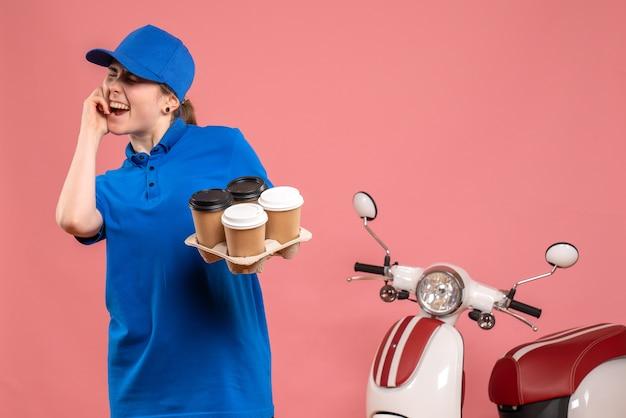 Vooraanzicht vrouwelijke koerier met bezorgkoffie op roze vloerwerk levering baan uniform dienst werknemer fiets