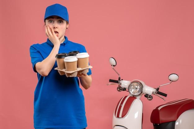 Vooraanzicht vrouwelijke koerier met bezorgkoffie op roze werk bezorgdienst werknemer fietsbaan