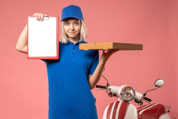Vooraanzicht vrouwelijke koerier met dossiernota en pizzadoos op roze Gratis Foto