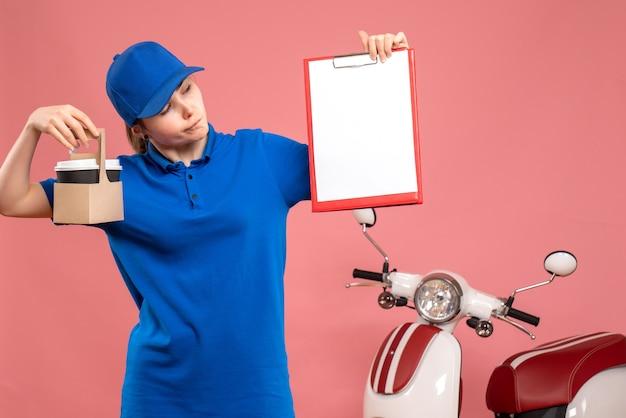 Vooraanzicht vrouwelijke koerier met koffie en dossiernota over de roze werk levering uniform dienst baan werknemer pizza vrouw fiets