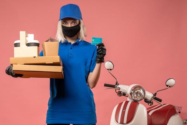 Vooraanzicht vrouwelijke koerier met koffievoedsel dozen en bankkaart op roze