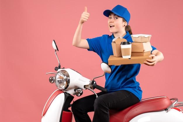 Vooraanzicht vrouwelijke koerier met voedselpakketten en dozen op de fietsdienst van de het voedselbezorgingsfiets van de baankleurarbeider