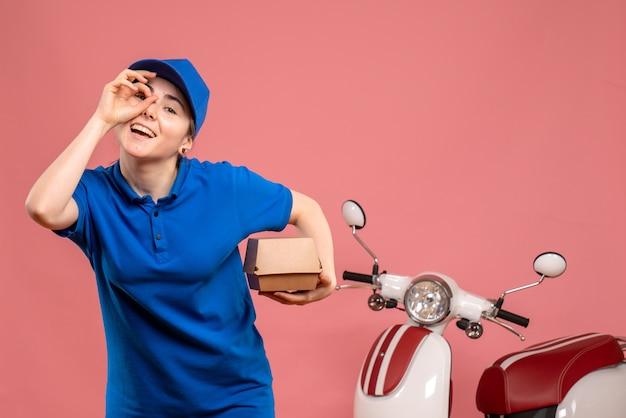 Vooraanzicht vrouwelijke koerier met weinig voedselpakket glimlachend op roze werk levering uniform dienst baan fiets werknemer pizza vrouw