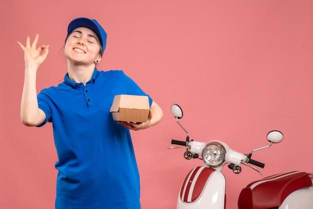 Vooraanzicht vrouwelijke koerier met weinig voedselpakket op roze werk levering uniform dienst baan pizza vrouw fiets