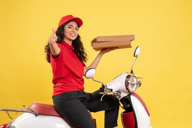 Vooraanzicht vrouwelijke koerier op de fiets met pizzadozen op gele achtergrond baan service uniforme bezorger werk
