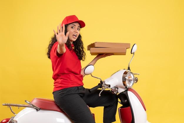 Vooraanzicht vrouwelijke koerier op de fiets met pizzadozen op gele achtergrond baan service uniforme werknemer vrouw levering werk