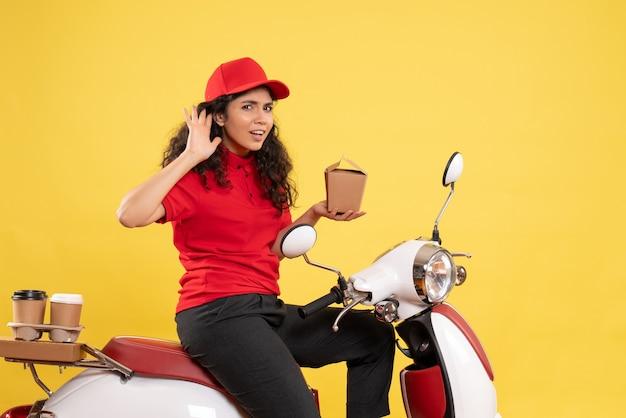 Vooraanzicht vrouwelijke koerier op de fiets voor koffie en eten bezorgen op een gele achtergrond service werk levering uniform werknemer baan vrouw
