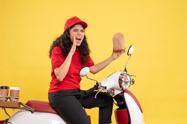 Vooraanzicht vrouwelijke koerier op de fiets voor koffie en eten bezorgen op gele achtergrond baan service uniform werknemer vrouw bezorgwerk