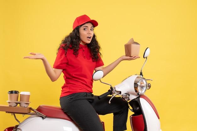 Vooraanzicht vrouwelijke koerier op de fiets voor koffie en eten bezorgen op gele achtergrond service werk bezorger job woman