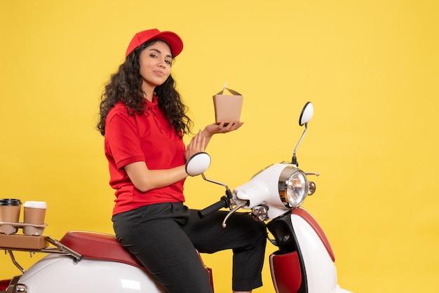 Vooraanzicht vrouwelijke koerier op de fiets voor koffie en eten bezorgen op gele achtergrond service werk levering uniforme baan vrouw