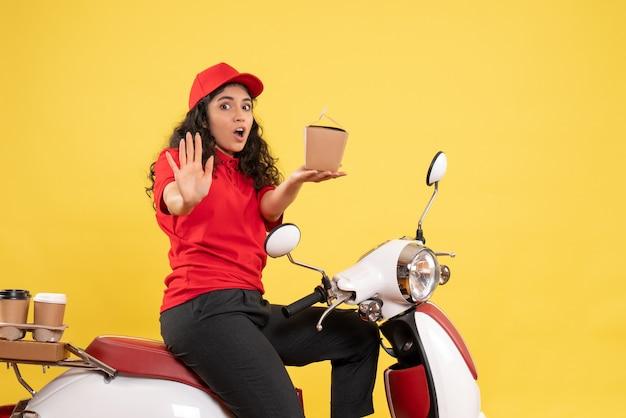 Vooraanzicht vrouwelijke koerier op de fiets voor koffie en eten bezorgen op gele achtergrond service werk levering uniforme werknemer vrouw uniform