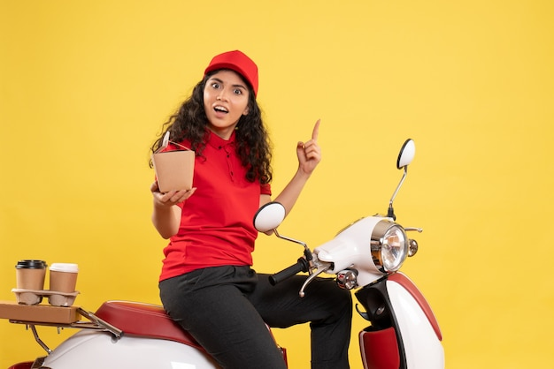 Vooraanzicht vrouwelijke koerier op de fiets voor koffie- en voedselbezorging op de gele achtergrond servicebezorging uniforme werknemer werk baan vrouw