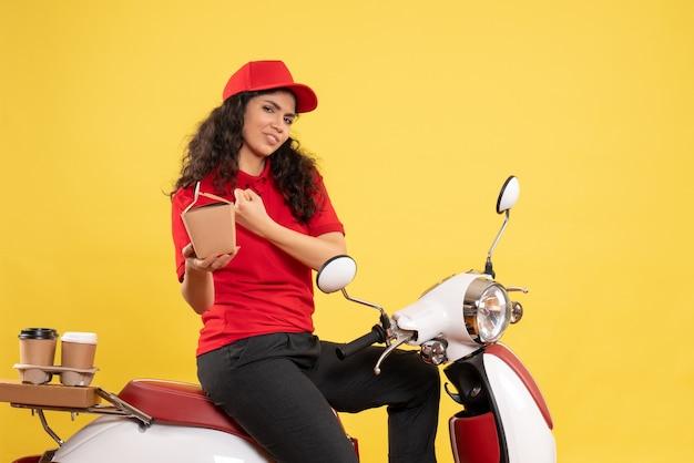 Vooraanzicht vrouwelijke koerier op de fiets voor koffie en voedselbezorging op gele achtergrond dienstbezorging uniforme werknemer baan vrouw